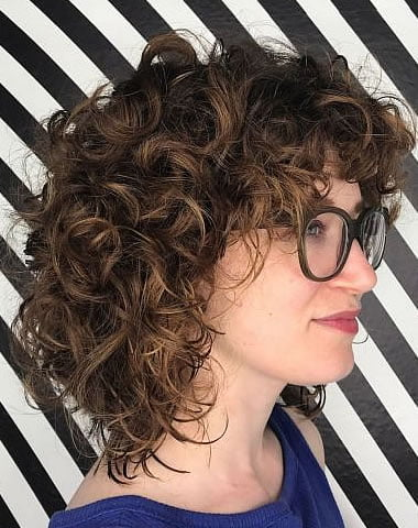 mid length curly hairstyle with bangs